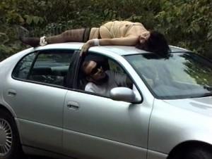 自動車の屋根に縛り付けられた女